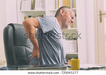 Man in home office suffering from low back pain sitting at the desk with notebook, papers and other objects #720045277