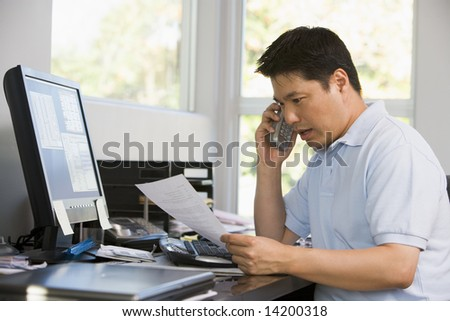 Man in home office with computer and paperwork on telephone