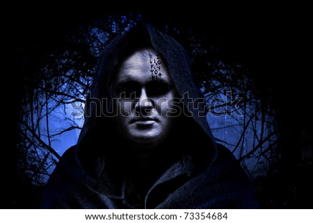 Man in hood on the spooky forest background.