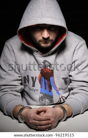Man in hooded jacket sitting at table in handcuffs. The face in the shadows
