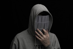 Man in hoodie and mask of playing cards on his face