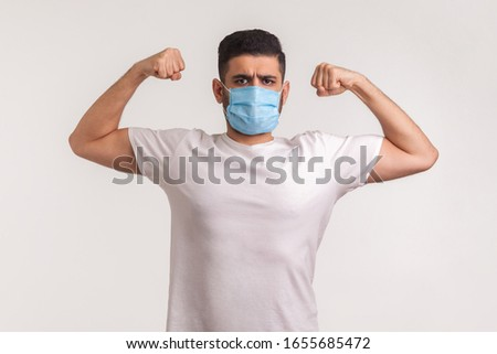 Man in hygienic mask showing strength and immunity to recover from contagious disease, airborne respiratory illness such as flu, coronavirus 2019-nCoV. indoor studio shot isolated on white background