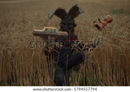 Man in image of sorcerer in hat with rabbit ears performs a voodoo ritual and holds doll impaled wire and old toy car on wheat field in evening. Сток-фото ©