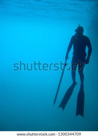 man in immersion freediving into blue of a submarine cave #1300344709