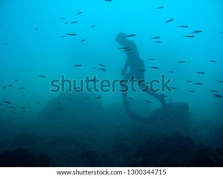 man in immersion freediving into blue of a submarine cave #1300344715