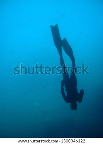 man in immersion freediving into blue of a submarine cave #1300346122