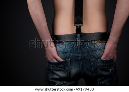 Man in jeans over black background. Back view