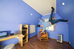 Man in jeans running on the ceiling upside down at inverted house