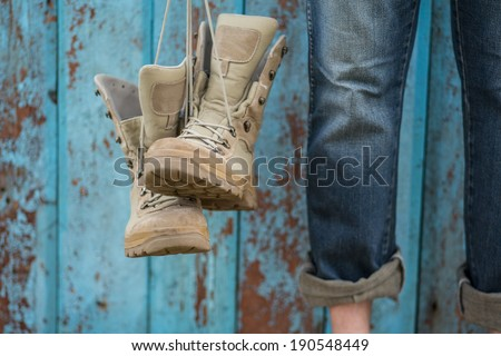 Man in jeans with his shoes over grunge blue wooden background. focus on nose shoe