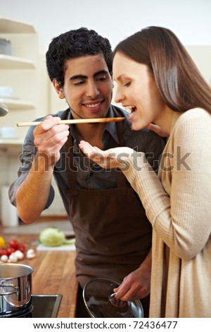 Man in kitchen letting woman taste a soup with a wooden spoon