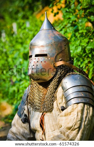 man in knight's helmet on a green background - stock photo