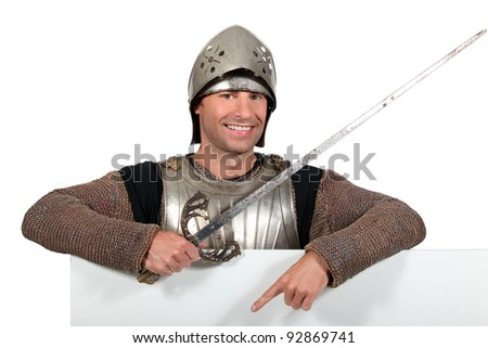 Man in knights costume pointing at blank board for your message #92869741