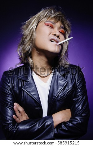 Man in leather jacket, wearing make-up, cigarette in mouth