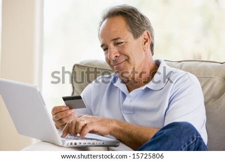 Man in living room with laptop and credit card smiling - stock photo