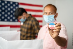Man in medical mask showing I voted Sticker at polling booth with US flag as background - concept in person voting at US election