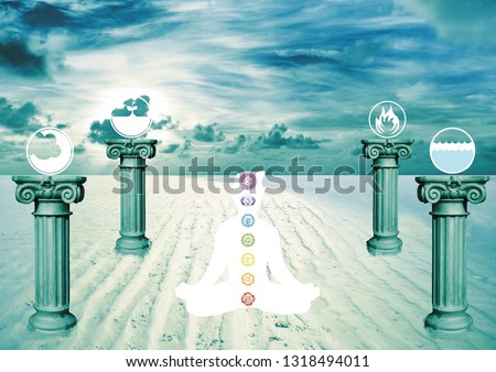 Man in meditation position with the 7 chackras on his body sitting on beach. Near him there are 4 pedestals with the four elements(air, earth, fire and water)-Spiritual,meditation in nature-Religion Stock photo ©