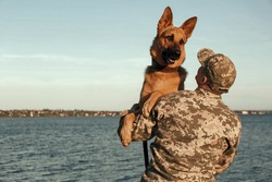 Man in military uniform with German shepherd dog outdoors