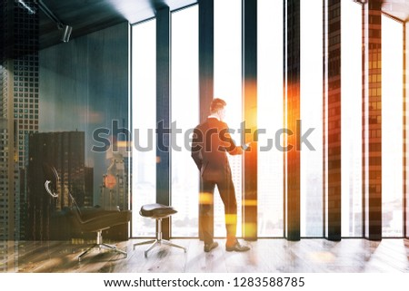 Man in minimalistic attic living room with dark wooden walls, wooden floor and brown armchair standing near the window. Toned image double exposure #1283588785