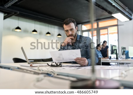Man in modern office start-up working on laptop.