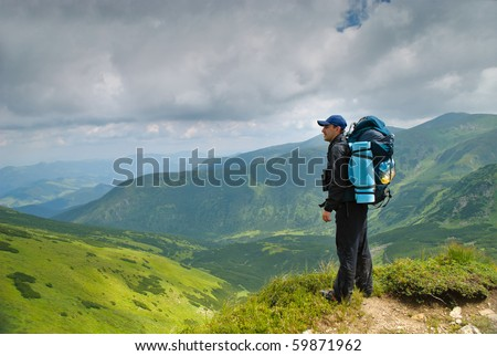 Man in montains with binocular and back pack look