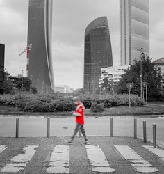 Man in motion blur on pedestrian crossing. The Citylife district skyline, made of tall towers with offices in the background. Overcasted dramatic sky. Monochromatic, exceps red. Milan, Italy.