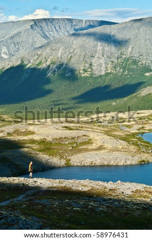 Man in mountain standing near lake and looking at camera from far away