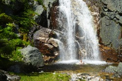 Man in mountains takes shower under cold huge waterfall. Wild nature anforgottable adventure.