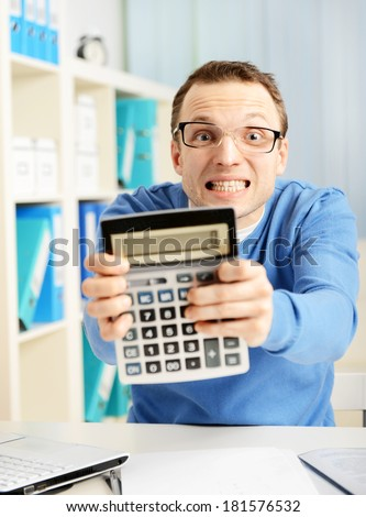 man in office, holding a calculator