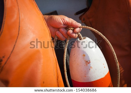 Man in orange overalls holding orange and white buoy with rope