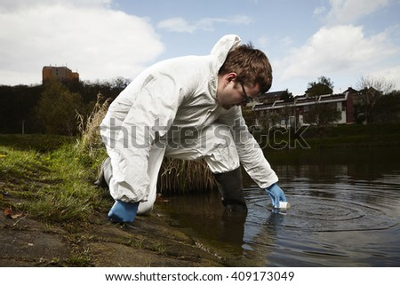 Man in overall protective suit collecting samples of water potentially contaminated by toxic material