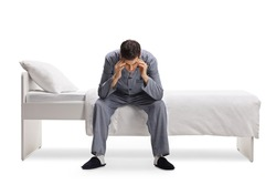 Man in pajamas sitting on a single bed and holding his head isolated on white background