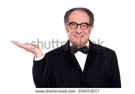 Man in party wear presenting copy space. Smiling at camera