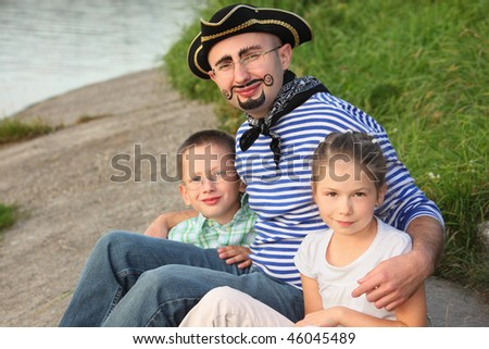 man in pirate suit with his son and daughter near pond in early fall park