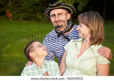 man in pirate suit with wife and son in early fall evening park
