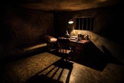 Man in prison man behind bars concept. Old dirty grunge prison miniature. Dark prison interior creative decoration. Miniature table inside. Selective focus