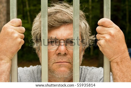 man in prison with hands wrapped around the bars