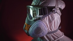 Man in protective costume suit, gas protect medical antibacterial antiviral spray paint mask. Doctor health worker in respirator. Concept health virus coronavirus epidemic. Radiation Nuclear war.