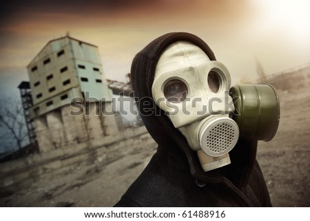 Man in protective gas mask near the industrial plant during radioactive sunset. Artistic colors and grain added