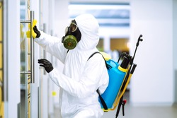 Man in protective hazmat suit washes door handles in office to preventing the spread of coronavirus, pandemic in quarantine city. Cleaning and disinfection of office. Covid-19.
