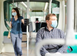 Man in protective medical mask and gloves rides in public transport