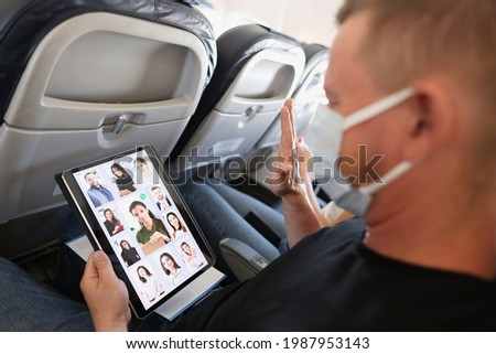 Man in protective medical mask conducts a remote business online conference via tablet while in transport