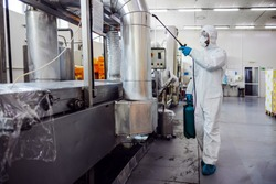 Man in protective suit and mask disinfecting machine for food production from corona virus / covid-19. Warehouse interior.