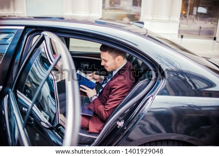 Man in purple suit looking in his notebook while sitting and working inside of a in limo automobile