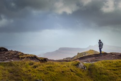 Man In Rain Jacket Looking Into The Distant Landscae From Top of Scottish Mountain