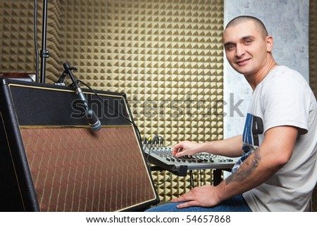 Man in recording studio sitting in front of mixer board. Guitar amplifier at foreground