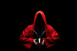Man in red ritual hooded cloak holds a skull with horns in hands. Religious sects, satanism concept. No face.