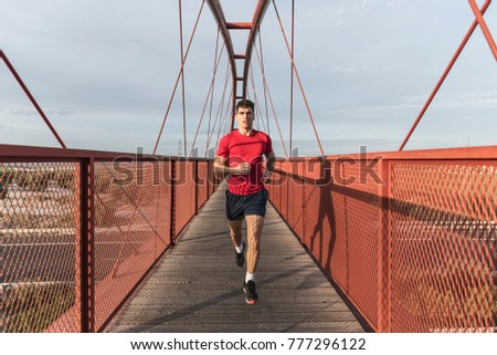 Man in red running on red bridge in sunset