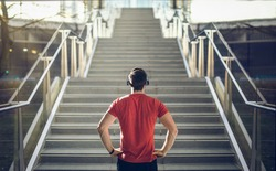 Man in red shirt preparing for stair run.