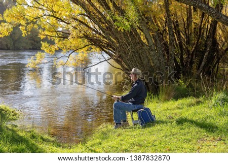 Man in retirement on holiday fly fishing for river trout