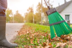 man in rubber boots sweeping autumn foliage at roadside in village street outdoor